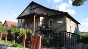 Dom od strony ulicy. Wejście do studia po drwenianych schodach po prawej stronie